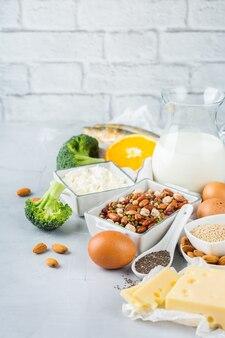 Zrównoważona dieta żywieniowa, koncepcja zdrowego odżywiania. asortyment źródeł żywności bogatych w wapń, fasolę, nabiał, sardynki, brokuły, nasiona chia, migdały na stole kuchennym. skopiuj tło przestrzeni