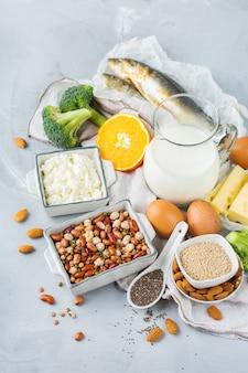 Zrównoważona dieta żywieniowa, koncepcja zdrowego odżywiania. asortyment źródeł żywności bogatych w wapń, fasolę, nabiał, sardynki, brokuły, nasiona chia, migdały na stole kuchennym