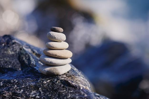 Zrównoważona kamienna piramida na brzegu błękitnej wody. scena leczenia kamieniami spa, zen jak koncepcje. żwirowa wieża nad morzem.
