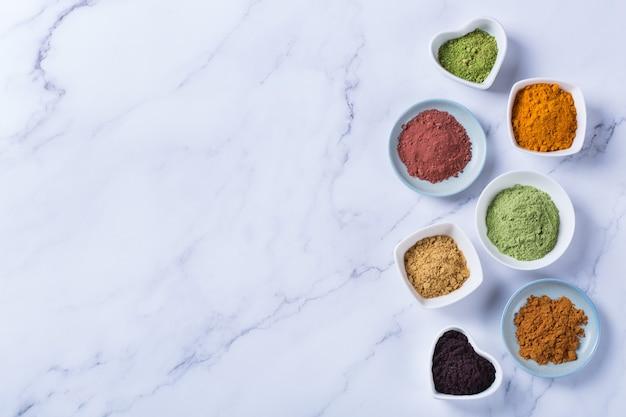 Zrównoważona koncepcja żywienia dla czystego odżywiania diety przeciwutleniającej. asortyment proszku superfood - acai, kurkuma, pszenica, imbir, cynamon, matcha. płaskie świecące, kopiujące tło marmurowe miejsce!
