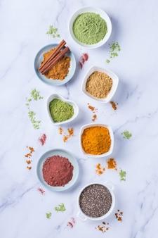 Zrównoważona koncepcja żywienia dla czystego odżywiania diety przeciwutleniającej. asortyment proszku superfood - acai, kurkuma, pszenica, imbir, cynamon, matcha. płaskie tło z marmuru