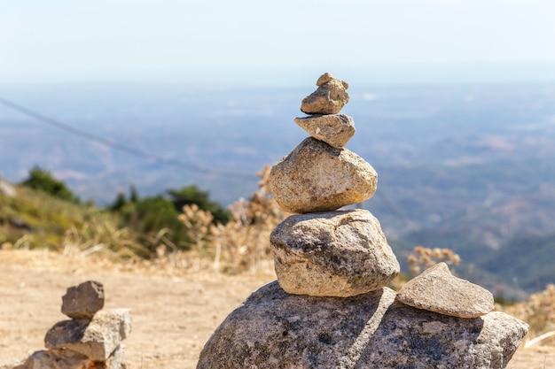 Zrównoważone kamienie stoją na wzgórzu z widokiem na algarve w portugalii