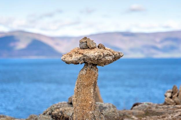 Zrównoważone kamienne piramidy na brzegu jeziora przypominają koncepcję równowagi i harmonii