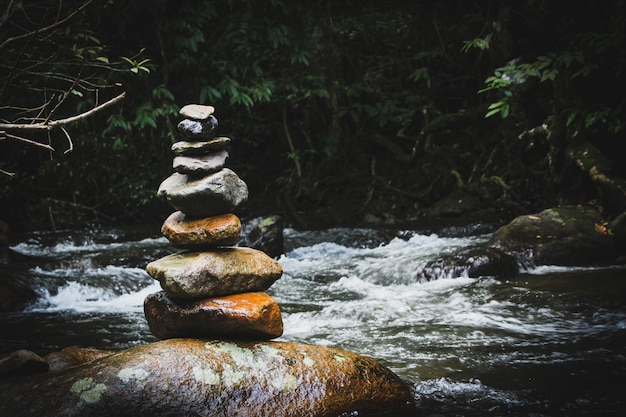 Zrównoważony kamienny piramidy na brzegu wodospadu górskiego jeziora. błękitne góry w lustrze poziomu wody. złe warunki oświetleniowe.