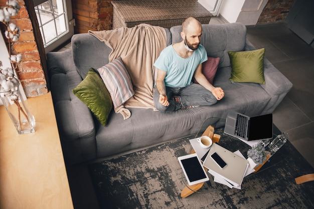 Zrównoważony. młody mężczyzna uprawiający jogę w domu podczas kwarantanny i niezależnej pracy online