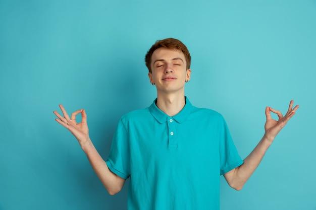Zrównoważony, spokojny. kaukaski nowoczesny portret młodego człowieka na białym tle na niebieskiej ścianie, monochromatyczne. piękny męski model. pojęcie ludzkich emocji, wyraz twarzy, sprzedaż, reklama, modne.