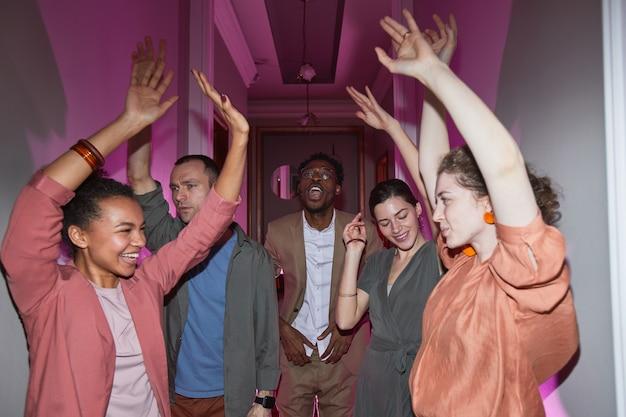 Zróżnicowana grupa beztroskich ludzi tańczących podczas zabawy w domu, kręconych z lampą błyskową