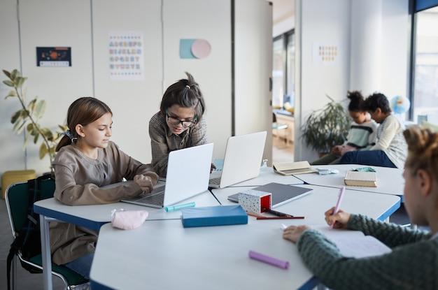 Zróżnicowana grupa dzieci pracujących razem przy biurku w klasie w nowoczesnej szkole, kopia przestrzeń