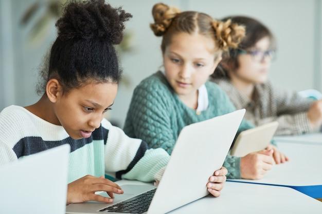 Zróżnicowana grupa dzieci siedzących w rzędzie w klasie szkolnej i korzystających z laptopów