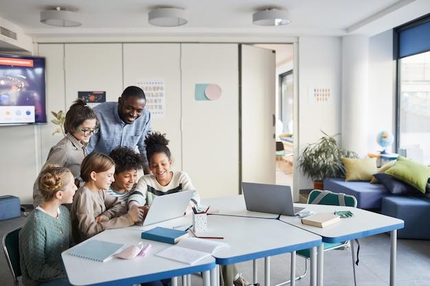 Zróżnicowana grupa dzieci z nauczycielem płci męskiej korzystających razem z laptopa w nowoczesnej klasie szkolnej, kopia przestrzeń