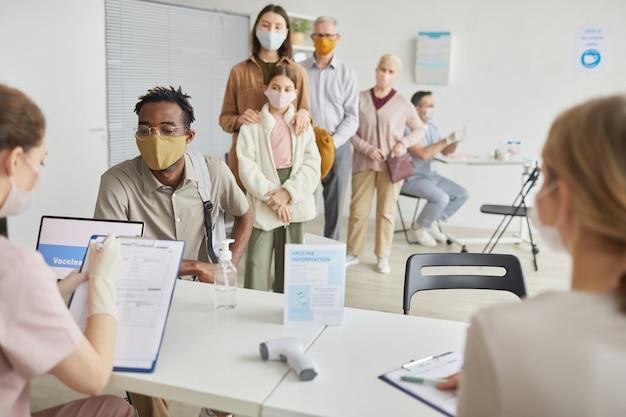 Zróżnicowana grupa ludzi czekających w kolejce, aby zarejestrować się po szczepionkę przeciw krowim w centrum szczepień, miejsce kopiowania