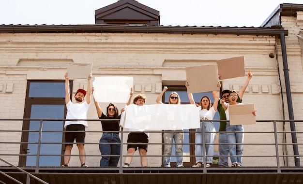 Zróżnicowana grupa ludzi protestujących pustymi znakami. protest przeciwko prawom człowieka, nadużywaniu wolności, problemom społecznym