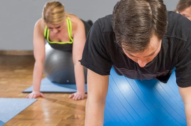 Zróżnicowana grupa ludzi w zajęciach gimnastycznych na matach wykonujących ćwiczenia pilates z piłką pilates
