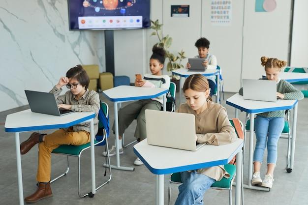Zróżnicowana grupa małych dzieci korzystających z laptopów siedzących przy biurkach w szkolnej klasie, kopia przestrzeń