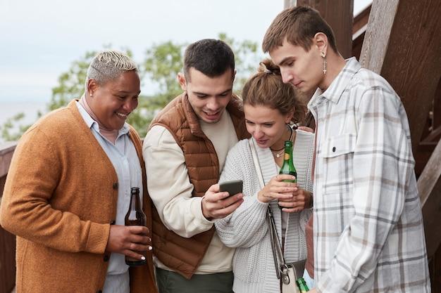 Zróżnicowana grupa młodych ludzi korzystających ze smartfona na balkonie podczas imprezy w domku nad jeziorem