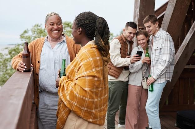Zróżnicowana grupa młodych ludzi pijących piwo na balkonie podczas imprezy w domu nad jeziorem