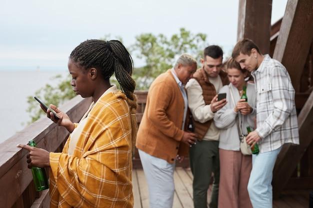 Zróżnicowana grupa młodych ludzi relaksuje się na balkonie podczas imprezy w domku nad jeziorem