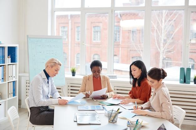 Zróżnicowana grupa odnoszących sukcesy biznesmenek omawiających projekt, siedząc przy stole przy oknie podczas spotkania w sali konferencyjnej