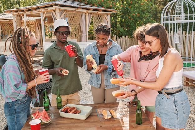 Zróżnicowana grupa przyjaciół pijących piwo i jedzących hot dogi przy stole na plaży, ciesząc się małą letnią imprezą
