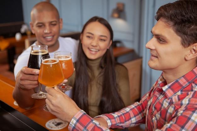 Zróżnicowana grupa przyjaciół razem pijących piwo w pubie