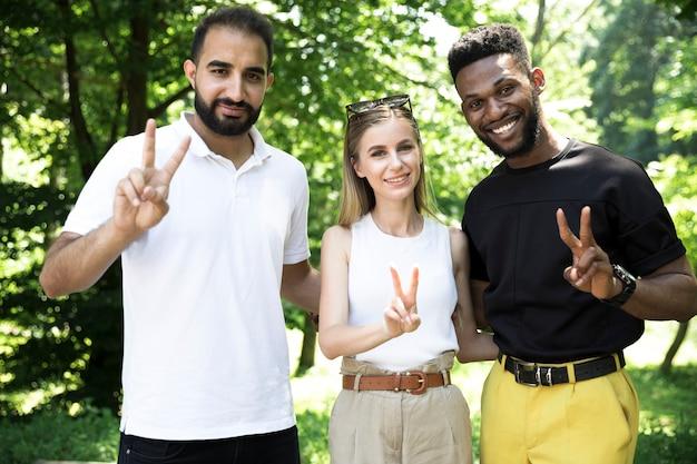 Zróżnicowana grupa przyjaciół robi znak pokoju