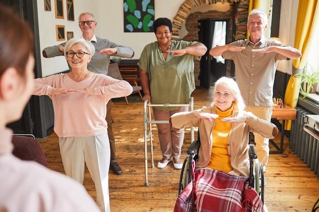Zróżnicowana grupa uśmiechniętych seniorów korzystających z porannych ćwiczeń w przestrzeni kopii domu starców