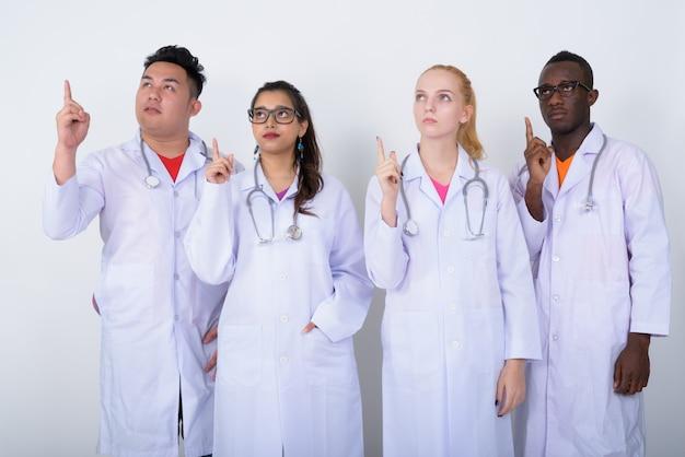 Zróżnicowana grupa wieloetnicznych lekarzy myślących, wskazując palcami w górę
