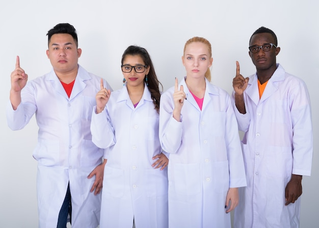 Zróżnicowana grupa wieloetnicznych lekarzy, wskazując palcem w górę