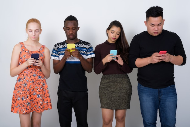 Zróżnicowana grupa wieloetnicznych przyjaciół korzystających z telefonów komórkowych