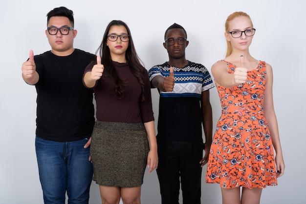 Zróżnicowana grupa wieloetnicznych przyjaciół rezygnujących z kciuka