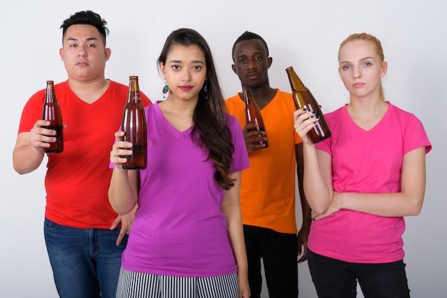 Zróżnicowana grupa wieloetnicznych przyjaciół trzymających butelki