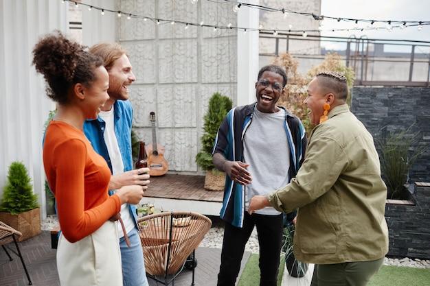 Zróżnicowana grupa współczesnych młodych ludzi bawiących się na imprezie na dachu na świeżym powietrzu, kopia przestrzeń