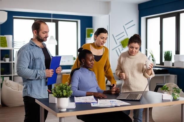 Zróżnicowana grupa współpracowników patrząca na kamerę w laptopie podczas spotkania wideokonferencji w start-upowym biurze firmy
