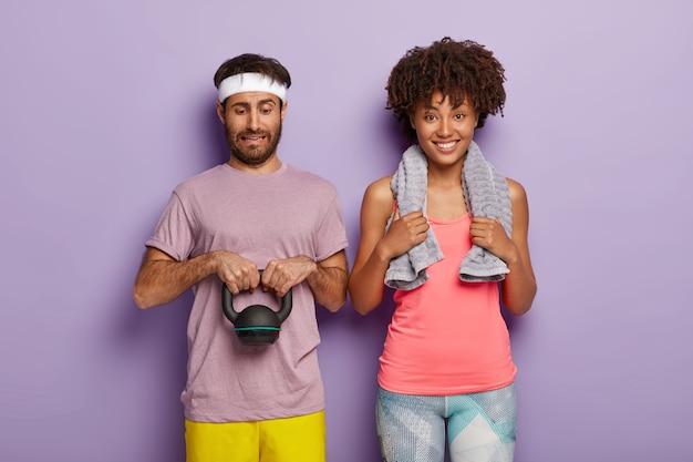 Zróżnicowana para ma trening cardio. przystojny mężczyzna podnosi ciężary