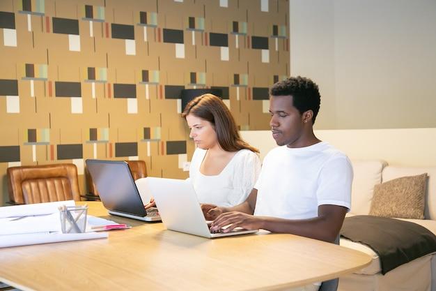 Zróżnicowana para projektantów siedzi razem przy stole z planami i pracuje nad projektem
