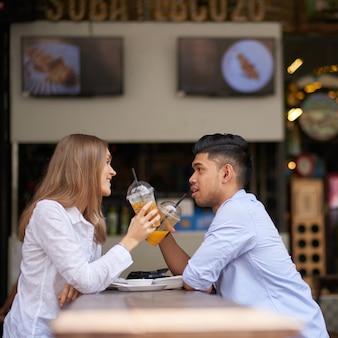 Zróżnicowana para siedzi przy stoliku kawowym, pijąc orzeźwiające napoje owocowe i rozmawiając