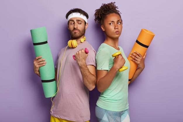 Zróżnicowana wysportowana para stoi z tyłu, trzyma hantle, maty fitness, ma pewną zdecydowaną mimikę