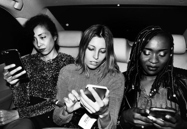 Zróżnicowane kobiety na tylnym siedzeniu taksówki