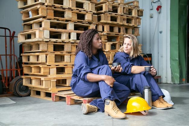 Zróżnicowane pracownice fabryki rozmawiają przy kawie, jedzą ciasteczka, siedzą na drewnianej palecie