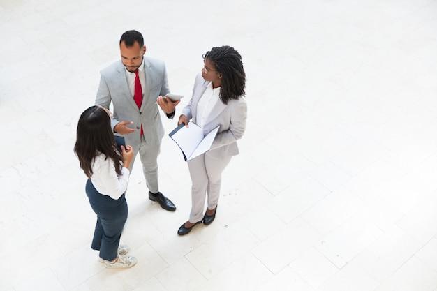 Zróżnicowane spotkanie biznesowe zespołu w korytarzu biurowym