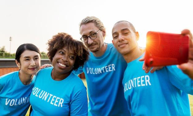 Zróżnicowani wolontariusze biorący selfie razem