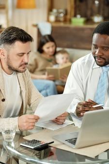Zróżnicowany konsultant i klient z papierami, siedzący przy stole z laptopem i maszyną liczącą, rozmawiając o kredycie hipotecznym