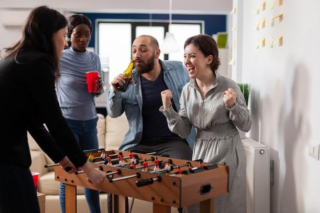 Zróżnicowany zespół kolegów grający po pracy piłkarzyki w piłkę nożną. wieloetniczna grupa ciesząca się wesołą zabawą podczas picia alkoholu z kubków w biurze