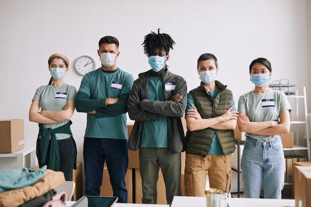 Zróżnicowany zespół wolontariuszy noszących maski, stojąc ze skrzyżowanymi rękami podczas akcji pomocy i darowizny, kopia przestrzeń