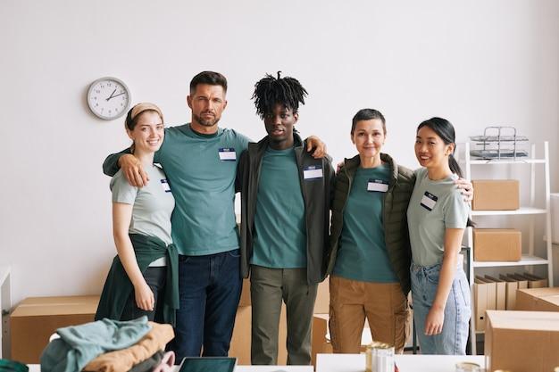 Zróżnicowany zespół wolontariuszy uśmiecha się do kamery i obejmuje podczas akcji pomocy i darowizny, kopia przestrzeń
