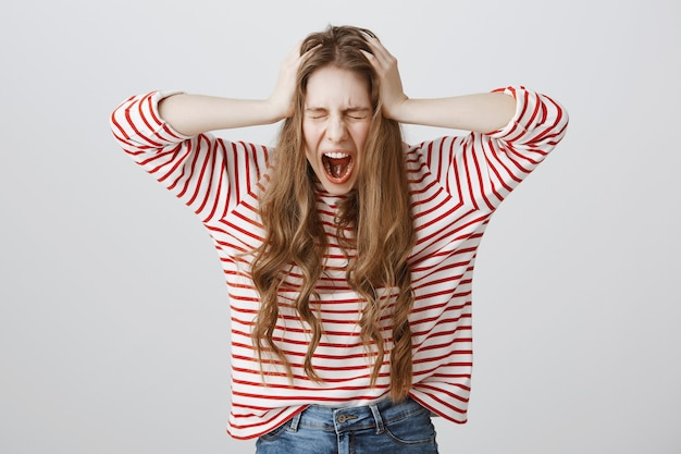 Zrozpaczona dziewczyna krzyczy i kręci głową w zaprzeczeniu, wyglądając na przygnębioną