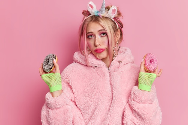 Zrozpaczona nieszczęśliwa kobieta nosi ciepły płaszcz z jednorożcem na głowie i sportowe rękawiczki trzyma dwa glazurowane pączki stara się unikać spożywania szkodliwych pokarmów trzyma się diety czuje pokusę