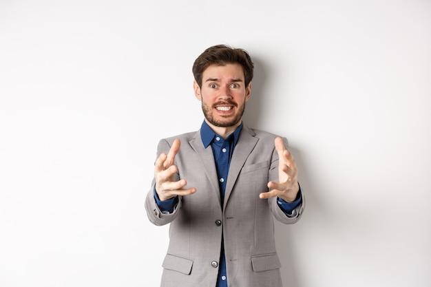 Zrozpaczony biznesmen wyciąga ręce, aby udusić irytującą osobę, stojącą zirytowaną i sfrustrowaną na białym tle, w garniturze.