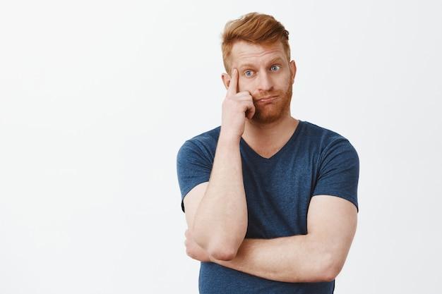 Zrozpaczony zmęczony i zmęczony przystojny rudy dojrzały mężczyzna z włosiem, wydech, trzymający palec na skroni i spoglądający w dół z zirytowanym i zmartwionym wyrazem twarzy