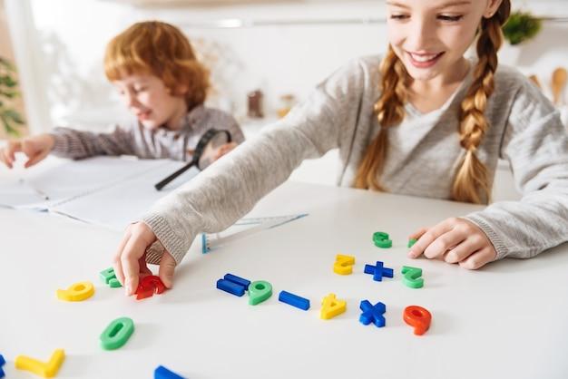 Zrozumiałe kolory. sprytna, troskliwa pozytywna dziewczyna uczy swojego uroczego rudego brata kilku arytmetyki, używając specjalnych kolorowych liczb i układając je w odpowiedniej kolejności
